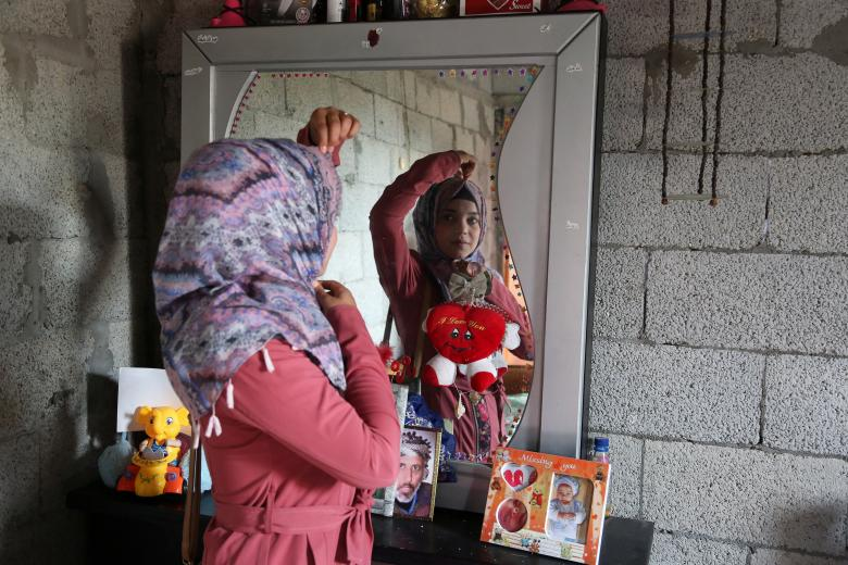 Shorouq Abu Musameh, who volunteers with other paramedics to treat wounded Palestinians participating in protests at the Israel-Gaza border, is reflected in a mirror as she adjusts her head cover in the southern Gaza Strip